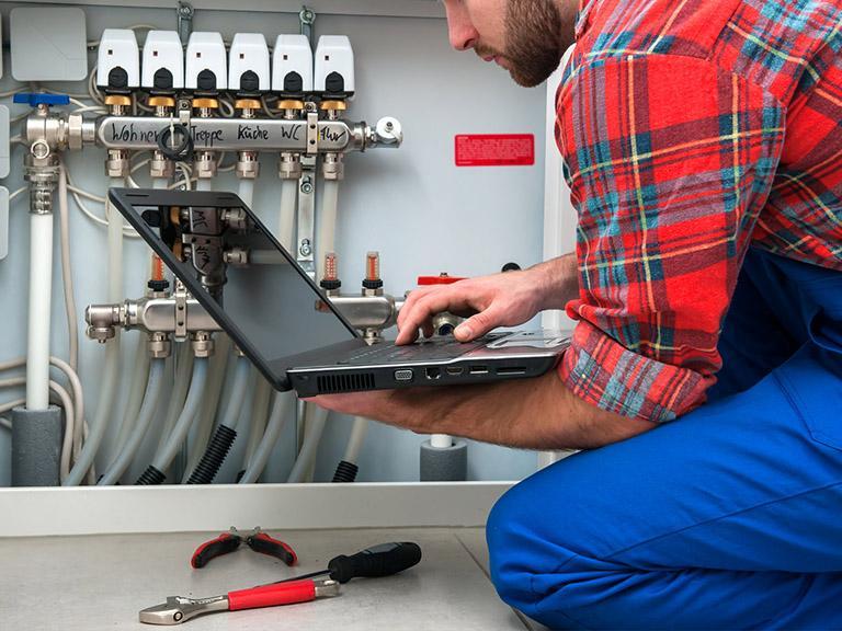Serwisant używający laptopa dodiagnozy